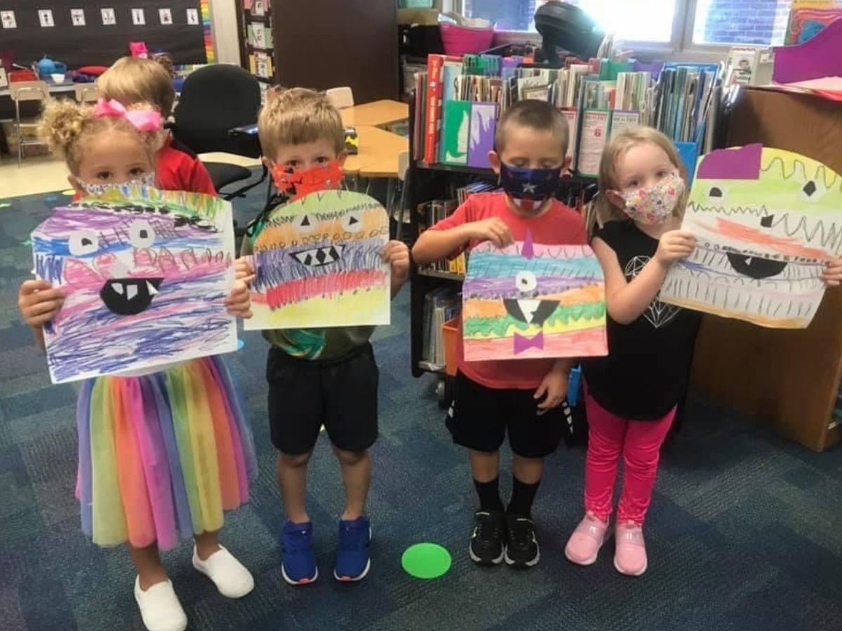 students holding monster artwork