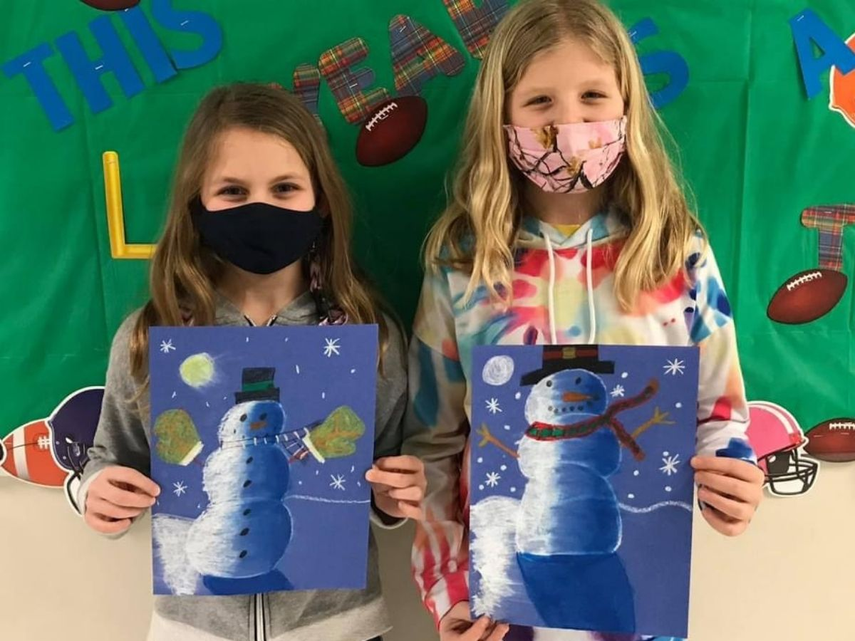 students holding snowmen art pictures
