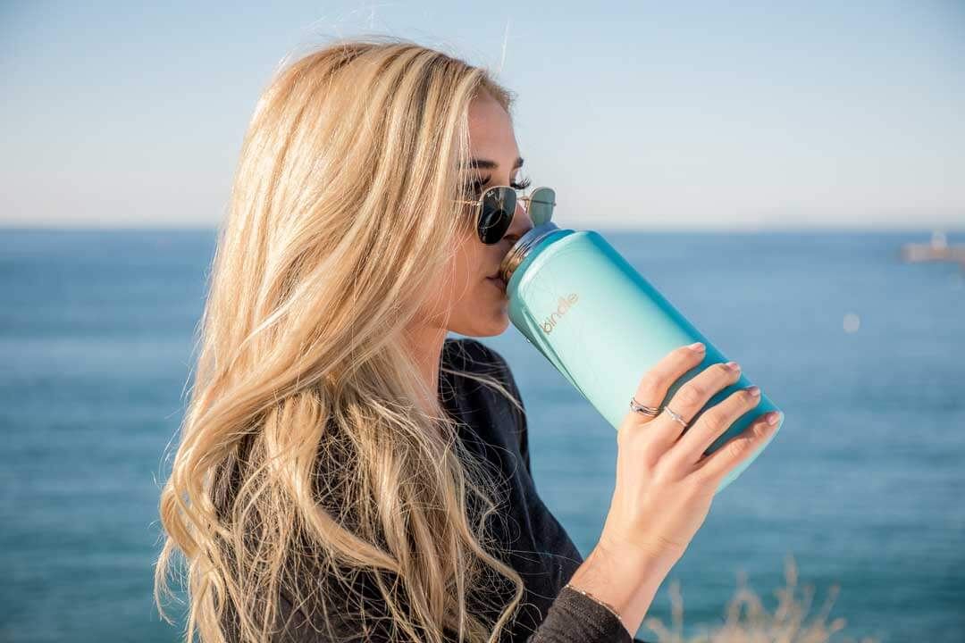 Blonde woman with sunglasses drinking water from a blue thermos near the ocean.