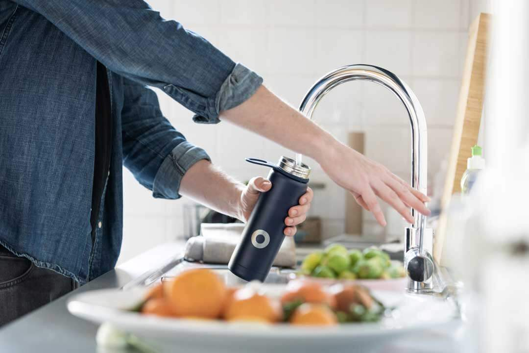 A woman's hands are shown filling up a block water bottle from the kitchen sink.