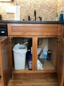 a sink cabinet with doors open to let warmer air reach the supply pipes