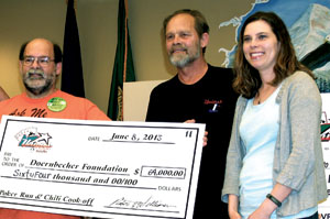 Unions for Kids committee members Rob Williamson and Lee Duncan present a check to Ashley Schmidt of the Doernbecher Foundation.