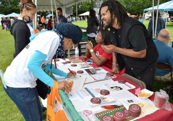 "Urban League staffers H.P. Nyanga and Alexandria Jones-Patten gather signatures in support of a ""ban the box"" ordinance June 28 at the annual Good in the Hood music and food festival in North Portland."