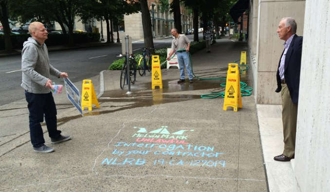 """David Zier (right), president of Melvin Mark Companies, questions Painters District Council 5 organizer Scott Oldham about his chalk work on the sidewalk outside of Melvin Mark's downtown Portland offices. Oldham showed up at 111 SW Columbia St. at 7:30 a.m. on June 3 to publicize anti-union actions by R&H Construction — a general contractor that Melvin Mark uses. Oldham chalked in the Melvin Mark logo and under it he wrote: """"Unlawful interrogation by your contractor: NLRB 19-CA-127019."""" Incidentally, no one was hosing the sidewalk when Oldham started chalking. The man in the background showed up about 10 minutes after Oldman began drawing."""