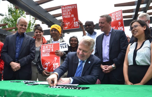 "Minimum wage campaigners celebrate as Seattle Mayor Ed Murray signs an ordinance creating a $15-an-hour city minimum wage. ""The economic policy of the 34 years has failed,"" Murray declared in a prepared statement. ""It has decimated the middle class, and it has created the largest income inequality gap in our history. Seattle is trying something else…. It's a step we recommend to other cities around the country."""