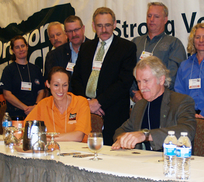 Oregon AFL-CIO communications and legislative director Elana Guiney watches as Oregon governor John Kitzhaber signs a bill at the 2013 state labor convention.