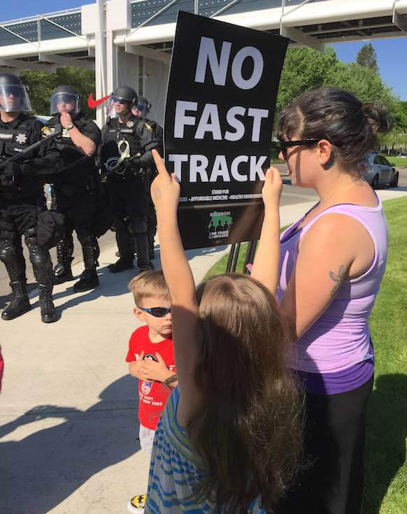 Riot police greet several young protesters at Nike World Headquarters May 8 as CEO Mark Parker welcomes President Barack Obama.