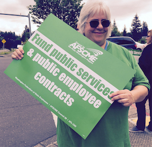 """On Thursday, June 18, 40,000-member Washington Federation of State Employees/AFSCME Council 28 held more than 90 """"Unity Rallies"""" around the state to stop a scheduled state shutdown on July 1. Above, a worker at Department of Social and Health Services walks the line in Vancouver."""