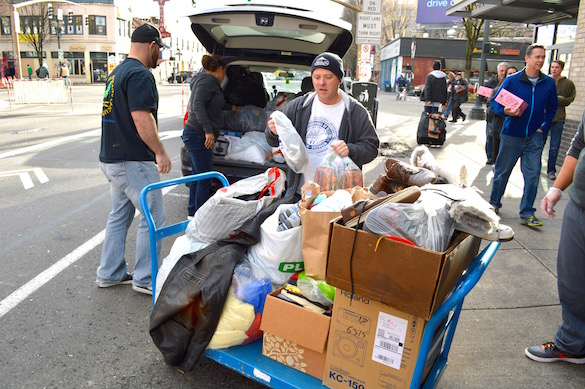 Business Rep Terry Reigle and apprentice Samer Obeid, left, unload a van stuffed with clothes and blankets donated by IBEW members.