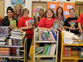 OSEA Central Chapter President Denise Chase, (fourth from right), along with fellow chapter members, helped sort books at French Prairie Middle School in Woodburn.