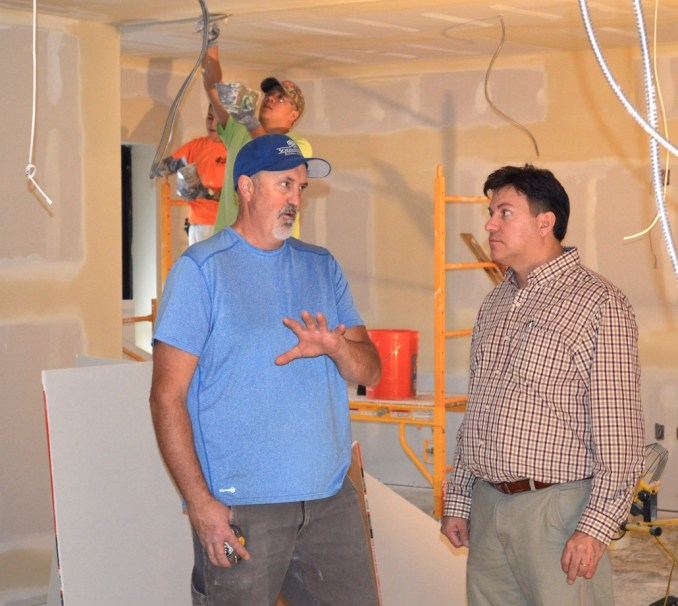 Jim Phelps (right), apprenticeship coordinator for the Painters & Tapers Training Center, talks to Kurt Moore project manager for Schommer and Sons Construction, as apprentice drywall finishers work in the background.