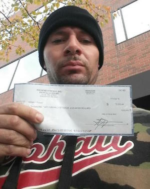 Instafab striker Will Russell holds up a check for backpay, part of a settlement approved Nov. 4 by the National Labor Relations Board.