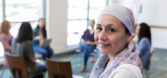 A woman wearing a headwrap smiles while attending a support group