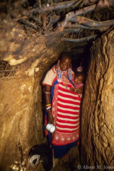 Kenya: Amboseli, Maasai (aka Masai) woman and baby in entrance to dung hut