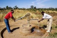 Kenya: Homa Bay, Nyauu DDCU, TechnoServe project using animal draft power for farming, two men pumping water from well.