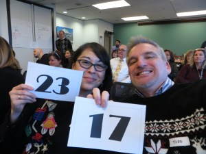 A woman and man holder auction bid number signs.