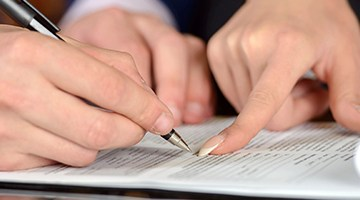 A man and female attorney signing a document