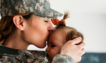 Military mom hugging with her child,