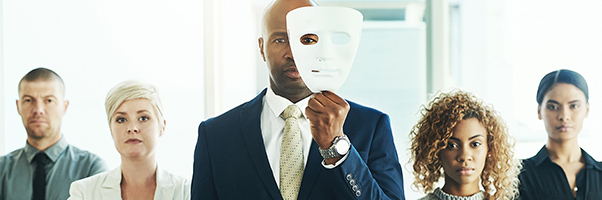 Portrait of a businessman holding a mask in front of his face with his colleagues standing alongside him in an office