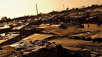 Journalist filming a Haitian refugee camp
