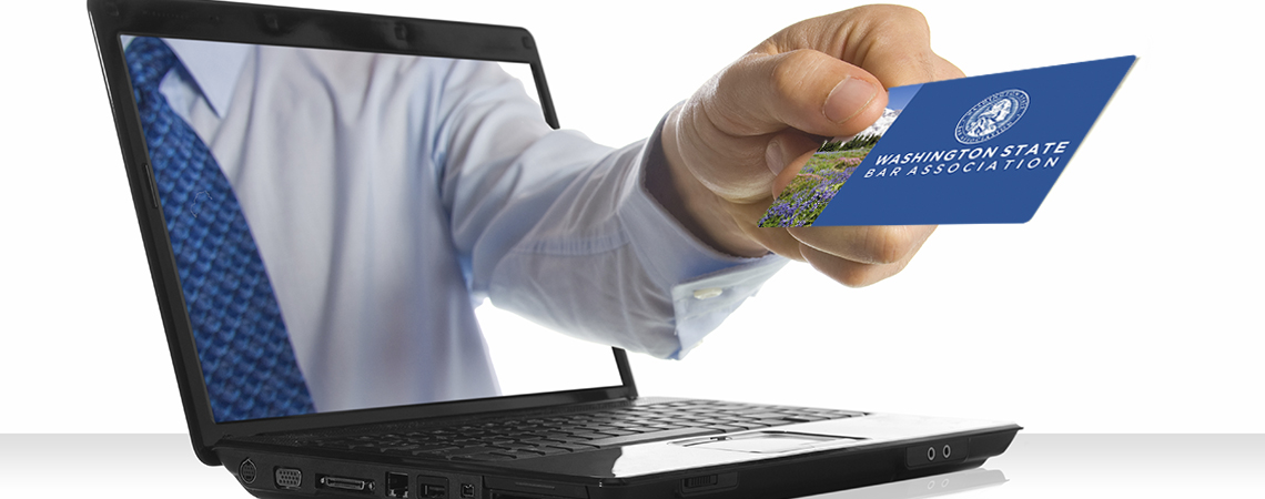 A hand sticking through a laptop giving a bar license card.