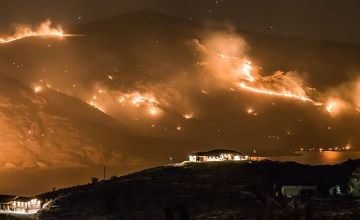 Night photograph of wildfires burning near Grand Coulee Dam in Grand Coulee Washington. Lake Roosevelt, part of the Columbia River reflects the wildfire.