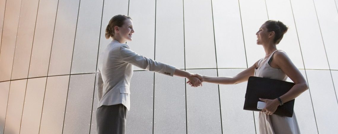 Women lawyers shaking hands outdoors