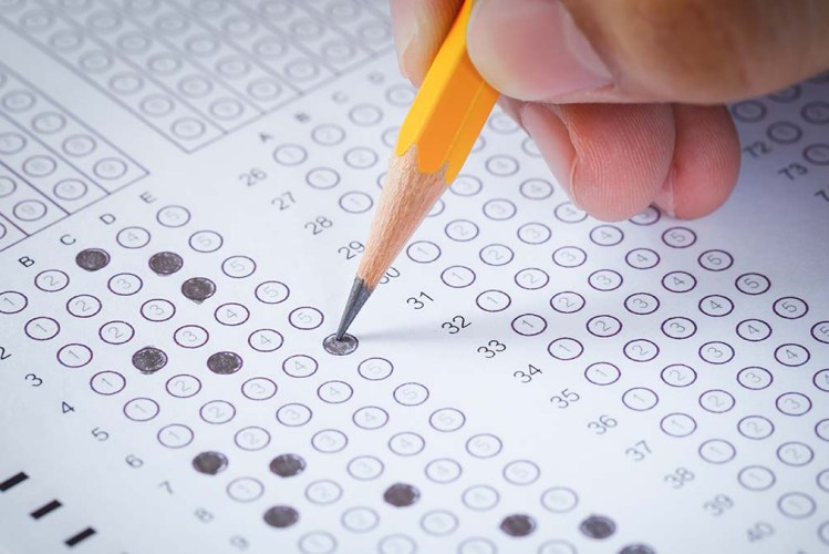 A hand using a pencil to fill out answers on the bar exam