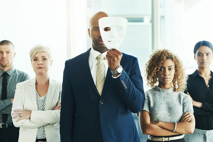 A male lawyer holding a mask in front of his face with his colleagues standing alongside him in a law office