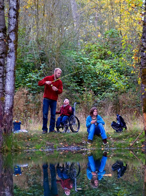 ANDREW RIGGS FISHES FOR TROUT WITH HIS SON, BLU, AND DAUGHTER HAYLEE, AT AN ODFW FAMILY FISHING EVENT AT ST. LOUIS PONDS NEAR WOODBURN. THE SITE FEATURES A PAVED PATH AND FISHING PLATFORMS, MAKING IT A GOOD CHOICE FOR ANGLERS WITH DISABILITIES. (RICK SWART, ODFW)