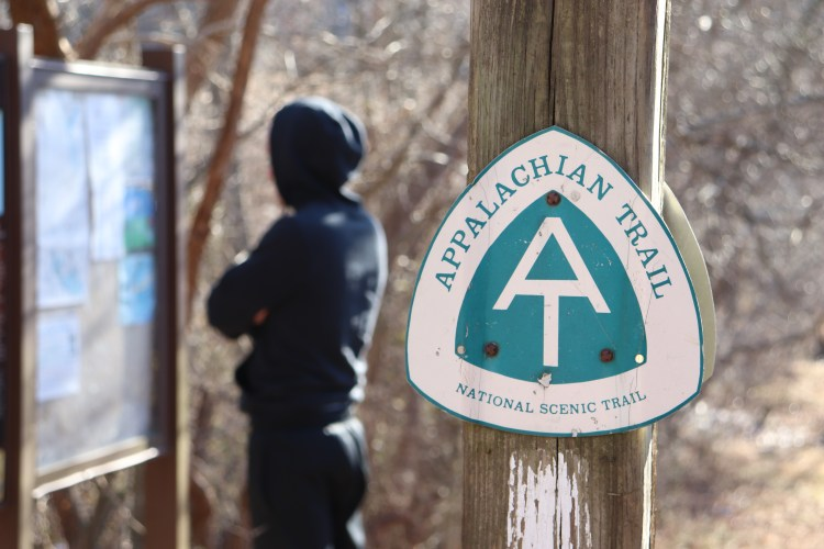 Image of an Appalachian Trail sign in the right foreground. In the background and out of focus, a man stands with his back to the camera looking at trail maps.