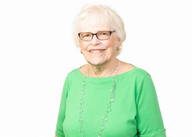 Image of Andrea Koenker. An older caucasian woman smiles at the camera. She has white hair and is wearing glasses. She wears a bright green blouse and a beaded necklace.