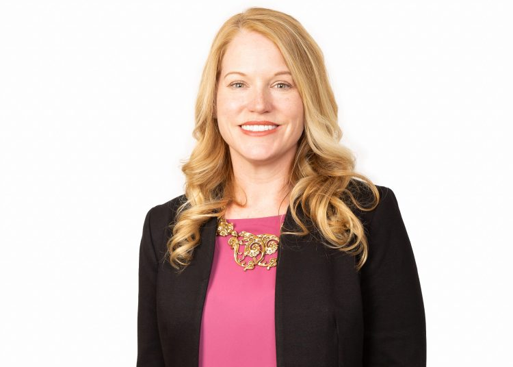 Image of Ann Wadsworth. A middle-aged caucasian woman with blonde hair smiles at the camera. She wears a pink blouse and a black blazer.