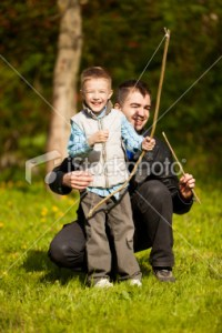 stock-photo-18021844-father-teaching-his-little-boy-using-bow-and-arrow