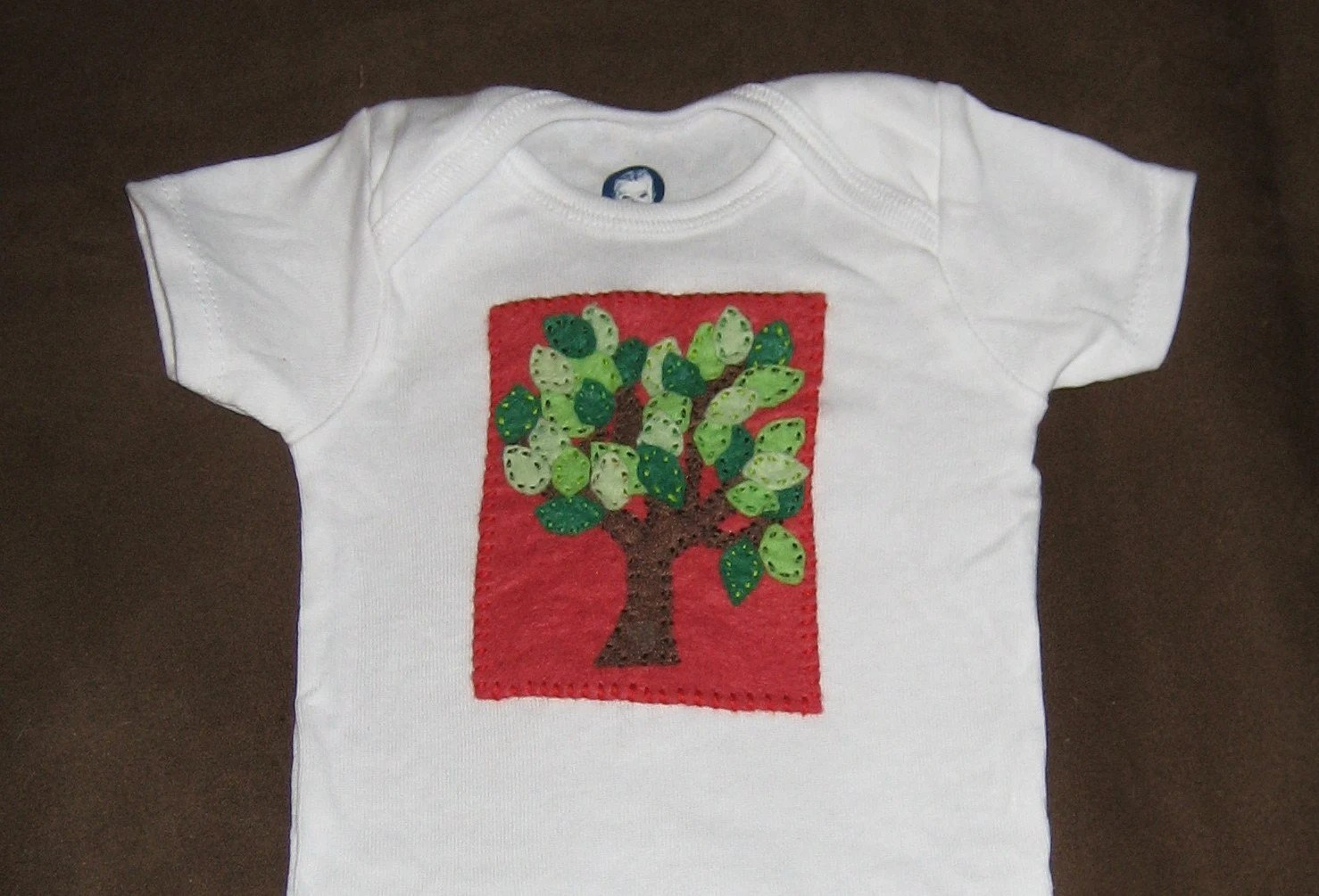 Tree on red background onesie