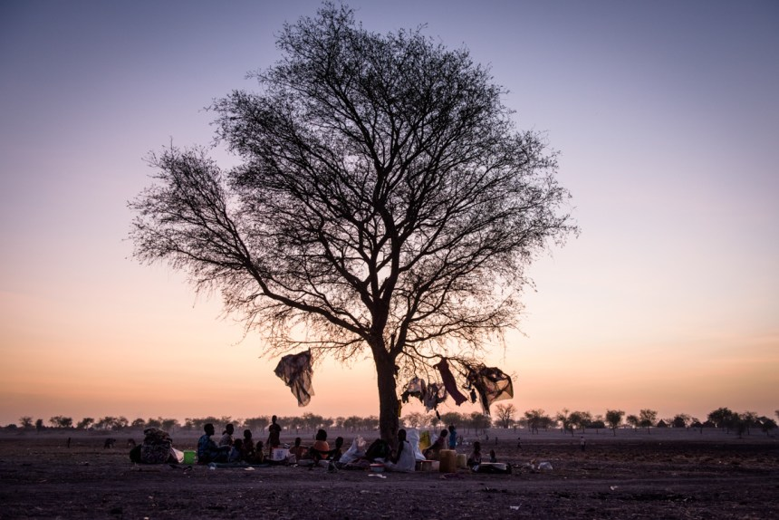 A family sit under a tree around which they live in the village of Aburoc, South Sudan, on May 11, 2017. Thousands of people, predominantly from the Shilluk tribe, have fled here after fighting forced them from their homes. Arriving in Aburoc with only what they could carry, many people are living outside in the open without any shelter.(Photo credit: Aljazeera/Phil Hatcher-Moore)