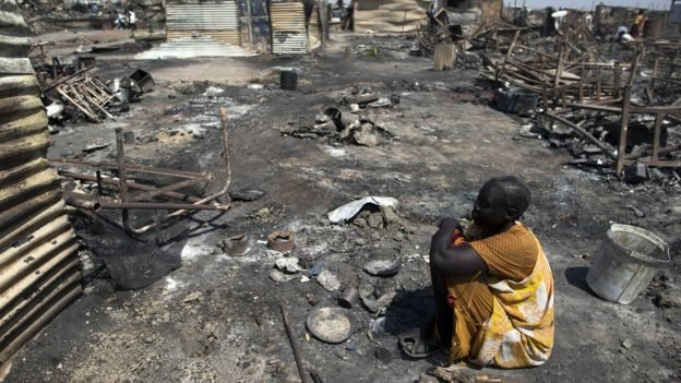 An elderly South Sudanese woman sits in a village that has been ransacked by soldiers after clashing with rebels in the area(Photo: file)