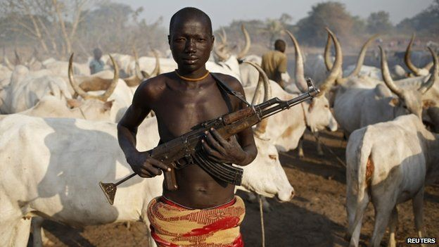 Armed Dinka tribesman in front of a cow herd in Lakes State, South Sudan (Photo credit: Reuters)