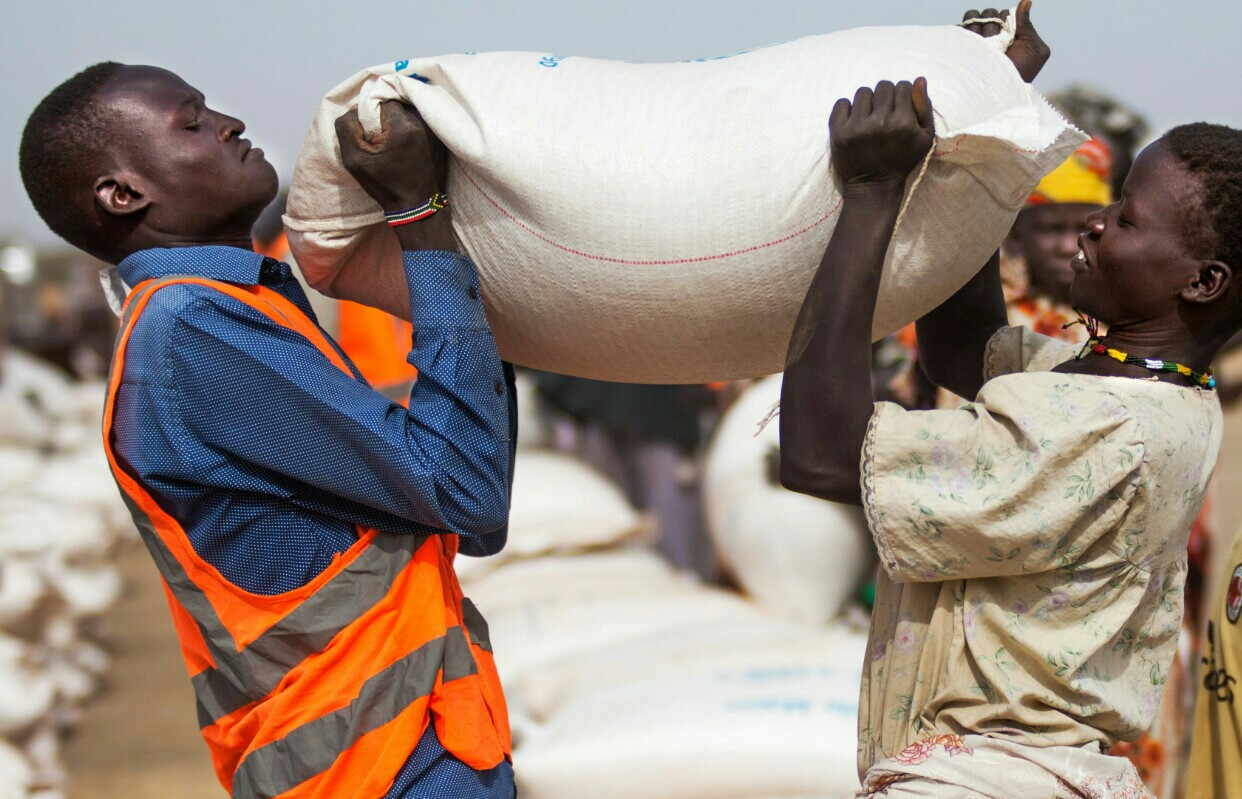 A aid worker helping a woman pocking up a sack of grain in an undisclosed location in South Sudan (File photo)