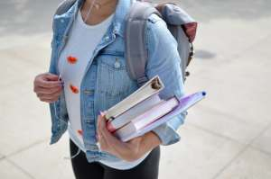 Girl with a backpack holding books