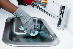 A person cleaning the sink in the kitchen, with rubber gloves and a cloth.