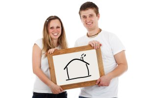 a couple holding a picture frame with a drawing of a house.