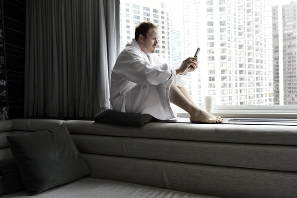 A man sitting by the window and checking a mobile phone.