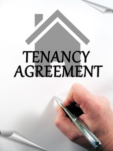A hand signing a Tenant agreement that can solve a great majority of problems NYC renters often face.
