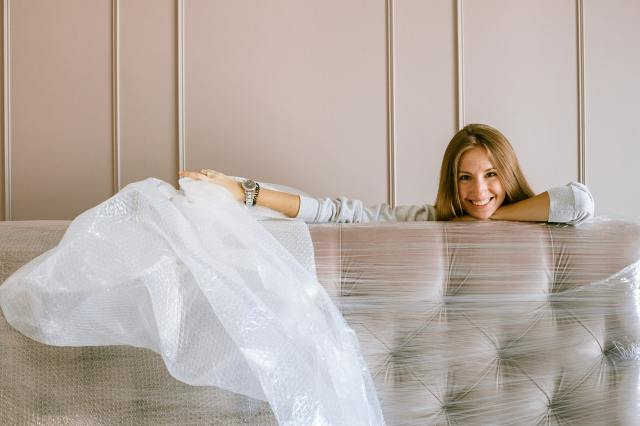 a woman holding a matress covered in wrapping material