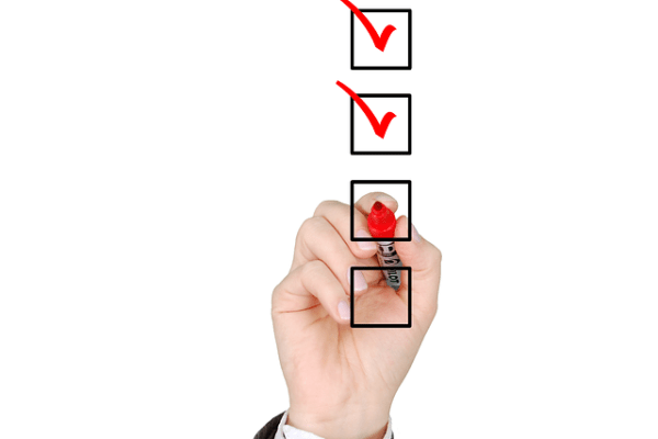 Checklist for a DIY cross-country relocation being thicked on a transparent board with a red pen.