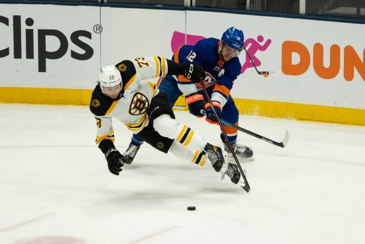 UNIONDALE, NY - JUNE 03: New York Islanders Right Wing Josh Bailey (12) and Boston Bruins Defenceman Charlie McAvoy (73) battle for the puck during the third period of Game 3 of the NHL Stanley Cup Playoffs Second Round between the Boston Bruins and the New York Islanders on June 3, 2021, at the Nassau Veterans Memorial Coliseum in Uniondale, NY. (Photo by Gregory Fisher/Icon Sportswire)