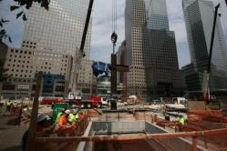 "A crane lowers the ""WTC Cross"" into the National September 11 Memorial and Museum.  Image credit:  National September 11 Memorial & Museum."