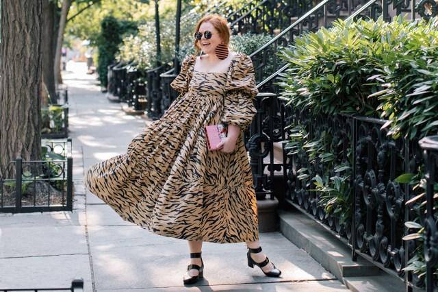 Девушка стоит на улице Нью-Йорка в коричнево-чёрном платье и улыбается