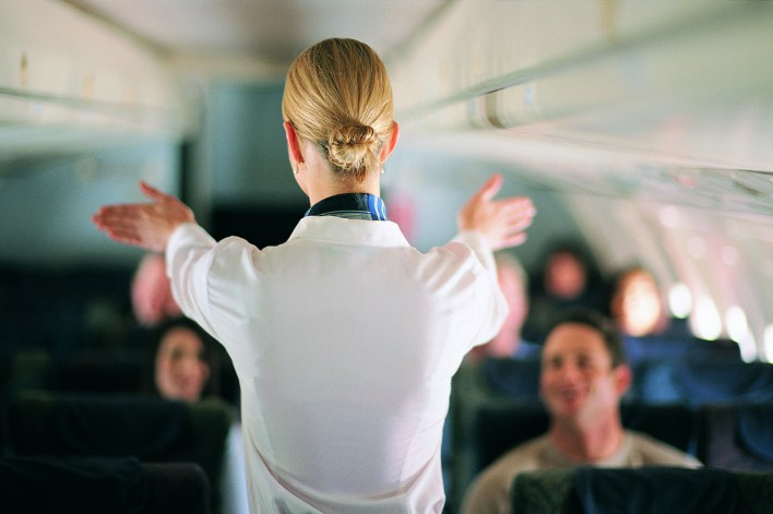 Rear View of Air Stewardess Explaining Aeroplane Safety to Passengers